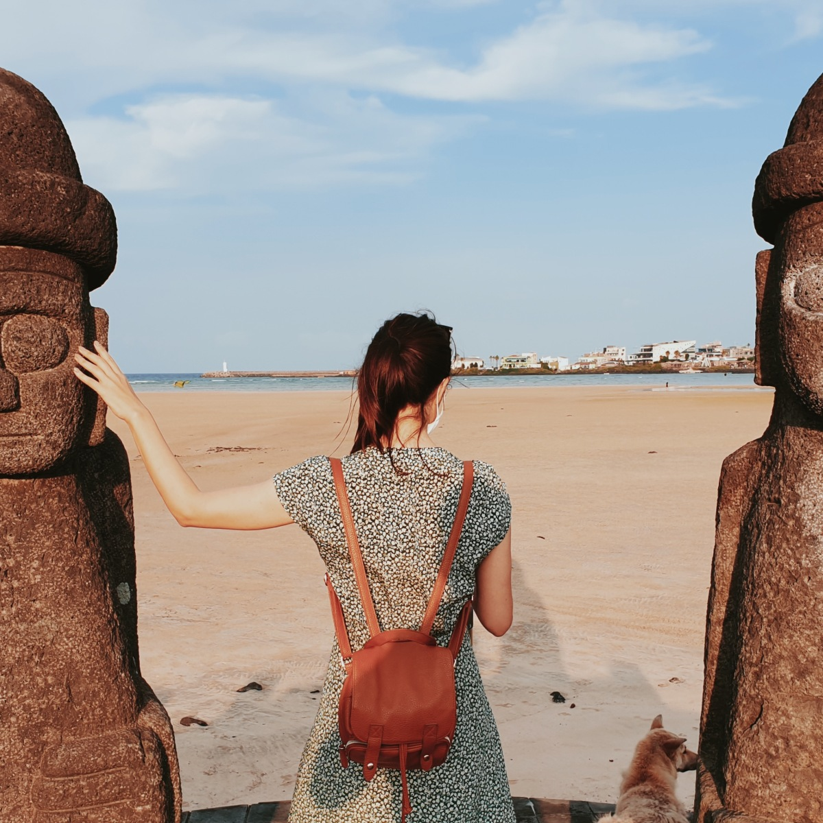 Sur une plage de l'ile de Jeju en Corée du Sud, je me tiens de dos entre deux statues en pierre typiques de l'ile.